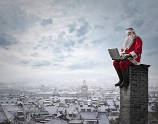 Image of Santa sitting on a chimney with a laptop